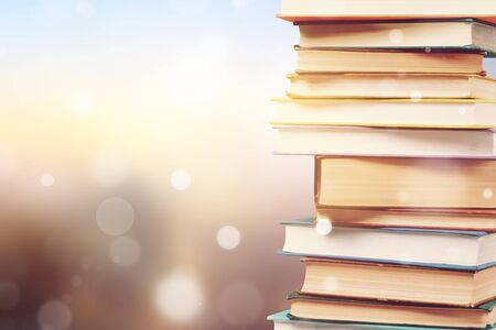 Stack of colorful books on blurred background