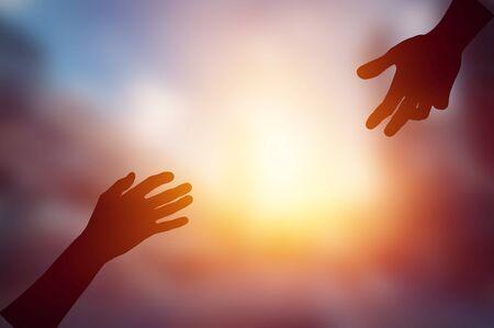 Help hand on sunset background Imagens