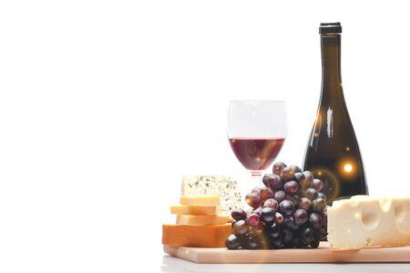 Bottiglia di vino, bicchiere di vino, formaggio e uva sul piatto di legno