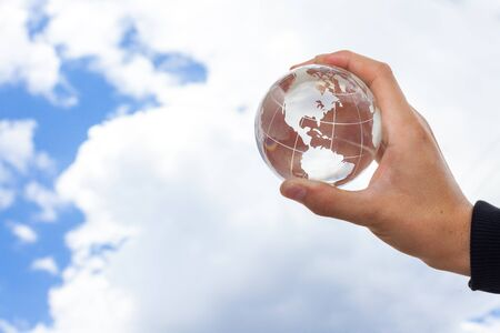Hand Holding Glass Globe Against Sky with Clouds