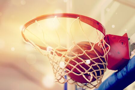 Orange basketball ball flying into the basketball hoop Banco de Imagens