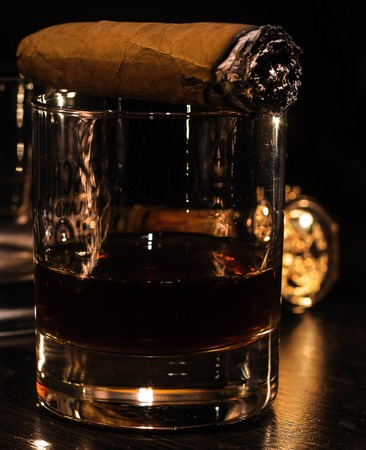 Still life with cognac, cigar , and a watch on a wooden background 스톡 콘텐츠