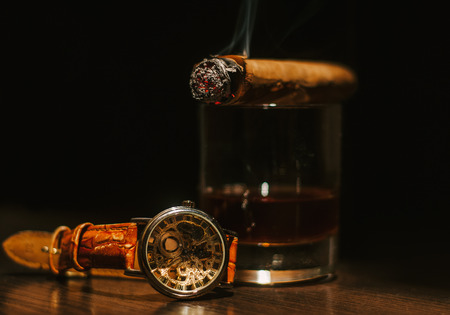 Still life with cognac, cigar , and a watch on a wooden background. close up shot
