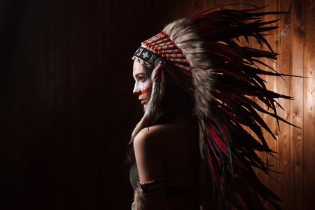 indian headdress: Indian woman with traditional make up and headdress looking to the side