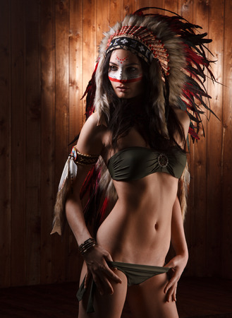 indio americano: Mujer india con maquillaje tradicional y un tocado mira a la cara