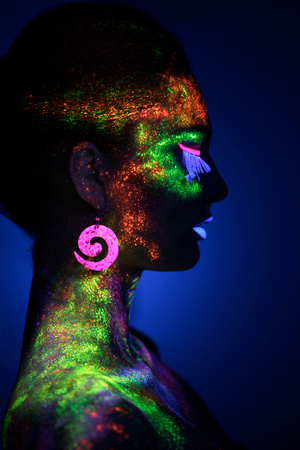luminescence: Sensual woman in fluorescent paint makeup. Luminescence paint. Dark blue background with copy space Stock Photo