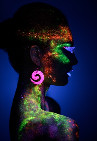 luminescence: Sensual woman in fluorescent paint makeup looking at the side. Luminescence paint. Dark blue background with copy space