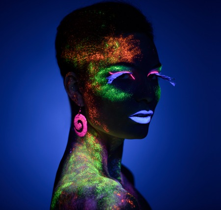 luminescence: Woman sensual posing in fluorescent paint makeup looking at camera. Luminescence paint. Dark blue background with copy space