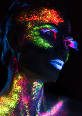 luminescence: Sensual woman in fluorescent paint makeup looking at the side. Luminescence paint. Dark background with copy space Stock Photo