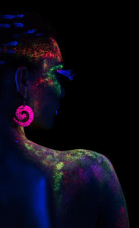 luminescence: Back of woman in fluorescent paint makeup looking at the side. Luminescence paint. Dark background with copy space