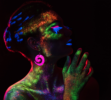 luminescence: Red  light contour on the sensual woman with fluorescent paint makeup. Model looking at the side. Luminescence paint. Dark background with copy space