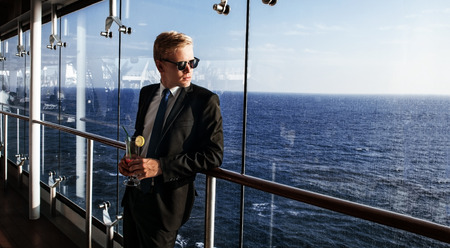 lux: Luxury life. Portrait of the handsome and rich man. Shot from cruise liner. Sea on the background with copyspace Stock Photo