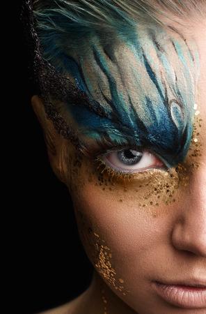 Young woman looking at camera with fantasy make up. Cose up Ususual face art studio shot. Half head Imagens - 34626995