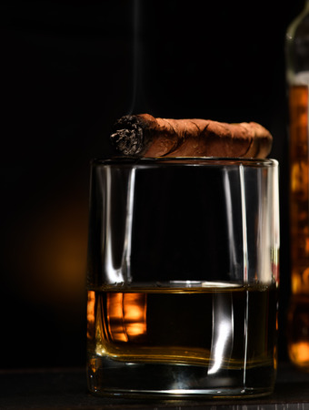 Luxury still life with cognac and cigar on a dark background. Close up shot with copyspace Stock Photo