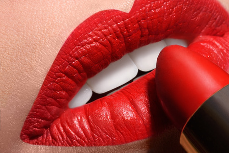 red tube: Sensual boca abierta con un tubo de l�piz labial rojo Macro foto de noche maquillaje labios Foto de archivo