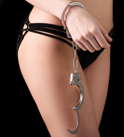 bdsm: Bdsm concept with handcuffs. Girl  in sey black lingerie. Part of body. Bdsm concept on black background