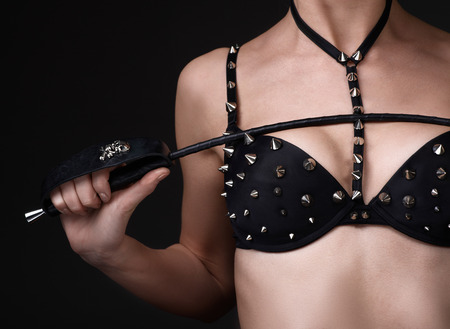 sensual nude: Sexy girl in black spiked bra play with lash. Bdsm concept no face. Copyspace Stock Photo