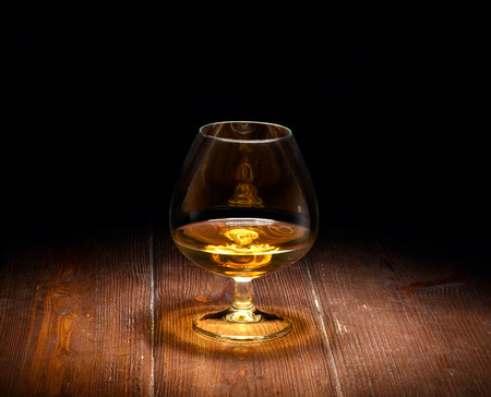 Luxury still life with glass of cognac, on a wood background. Front view with copyspace. Close up shot. photo