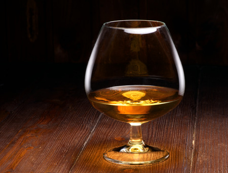 Luxury still life with glass of cognac, on a wood background. Front view with copyspace. Close up shot photo