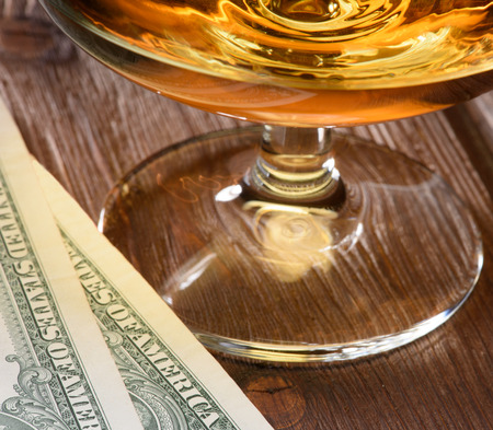lux: Close up luxury still life with glass of cognac and dollar bills on a wood background. Top view. High resolution Stock Photo