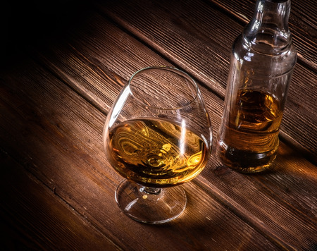 Luxury still life with glass of cognac, and bottle on a wood background. Top view with copyspace. High resolution photo