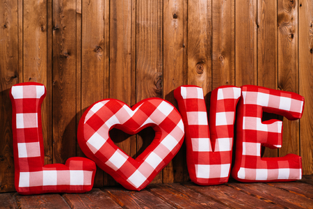 full day: Love word of plush red letters on wood background. Full plaid textile. February 14, Valentines Day concept shot with text space. Front view. High resolution Stock Photo