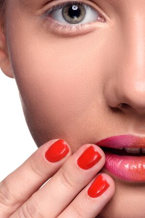 close up   head: Half face of sensual young woman with colorful lips makeup and red nails looking at the camera. Close up head shot