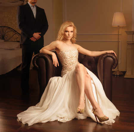 Luxury woman at armchair and man behind in rich interior