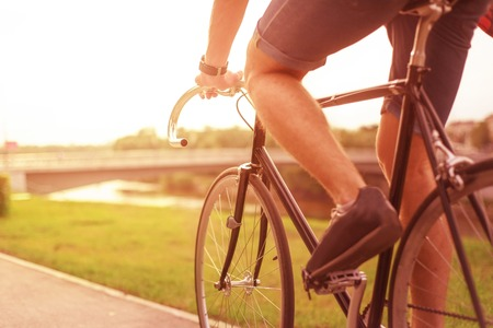 exercise bike: Hipster on bike in the city at sunset. Without face Stock Photo