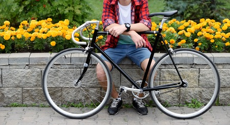 Hipster man with bicycle resting over flowerbed withal yellow flowers. Without face. Front view