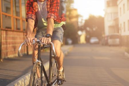 Close-up hipster op de fiets in de stad bij zonsondergang. Shot met sunflare en zonder gezicht.