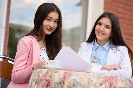 china people: Two Asian business woman with project. Looking at camera Stock Photo
