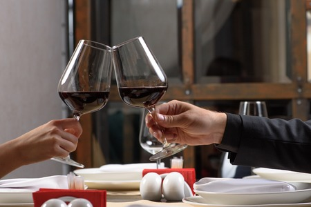 Couple drinking red wine in restaurant. Close-up hands with glasses. Stock Photo