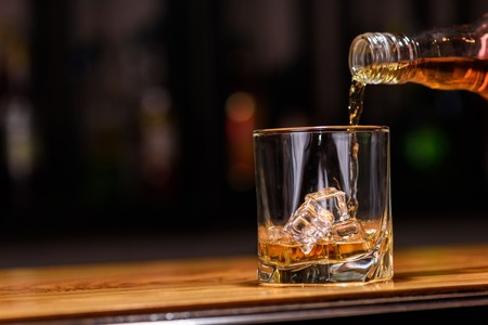 alcoholic drink: Still life. pour or whiskey in to glass. Stock Photo