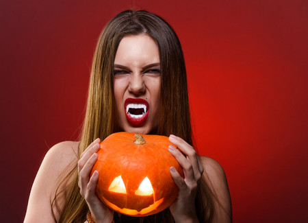 beautiful vampire: Lady Vampire with halloween pumpkin. Portrait of Brunette Woman over red background.