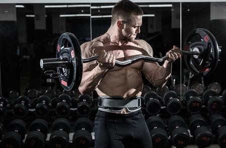 bodybuilder: culturista musculoso atleta en el bíceps entrenamiento de gimnasio con bar. Foto de archivo