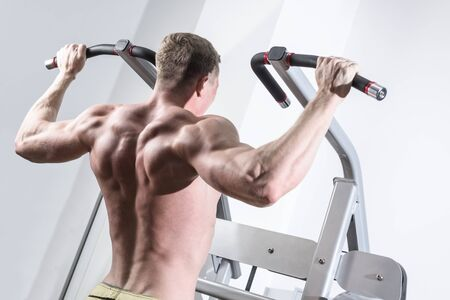 pullups: Bodybuilder training in the gym. Athlete doing Pull-Ups.