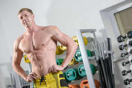 sexy abs: Fit bodybuilder posing in gym over stand with training equipment