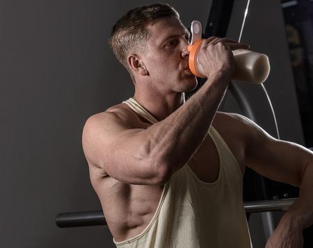 hombre deportista: Hombre del atleta beber prote�na en el gimnasio. Copyspace Foto de archivo