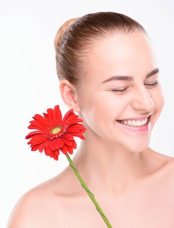 scincare: Cheerful beautiful woman with red gerbera. Isolated on white background. Stock Photo
