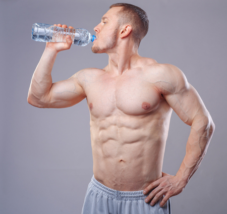 Athlete man drinking water over dark background. Stock Photo