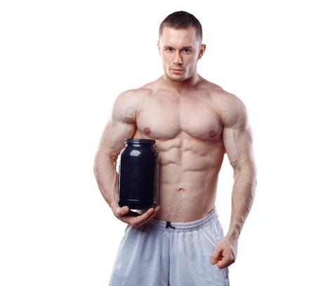 nutrientes: Bodybuilder que sostiene un frasco de plástico negro con proteína de suero aislada en el fondo blanco. Foto de archivo