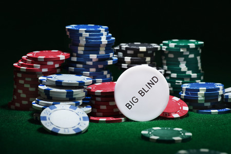 Close up shot of group poker chips on green table.