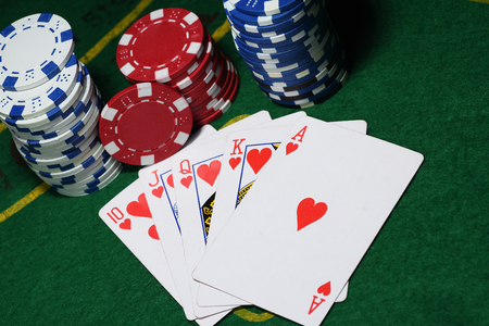 lear: Cards and chips for poker on green table, top view