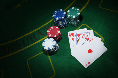 Cards and chips for poker on green table, top view