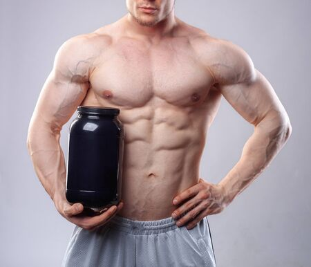nutrients: Bodybuilder holding a black plastic jar with whey protein on grey background. Without face Stock Photo