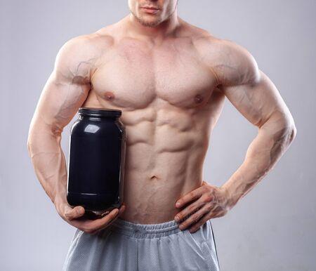 nutrientes: Culturista que sostiene un frasco de plástico negro con proteína de suero en el fondo gris. Sin rostro Foto de archivo