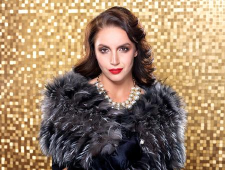 silver fox: Portrait of elegant brunette retro woman wearing silver fox fur over gold mosaic background.
