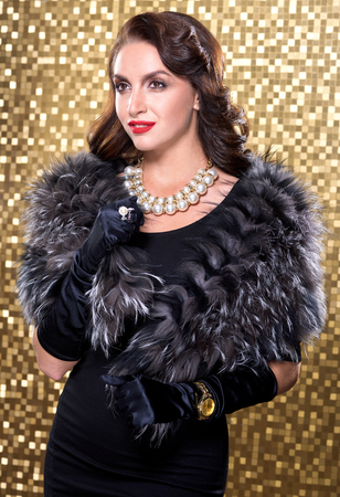 silver fox: Portrait of elegant brunette retro woman wearing silver fox fur over gold mosaic background. Model looking at the side.