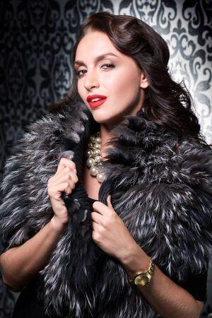 silver fox: Portrait of sexy brunette retro woman wearing silver fox fur over vintage background.